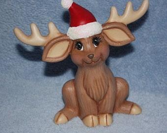 Handpainted Ceramic Calico Christmas Deer sitting up wearing a Santa hat