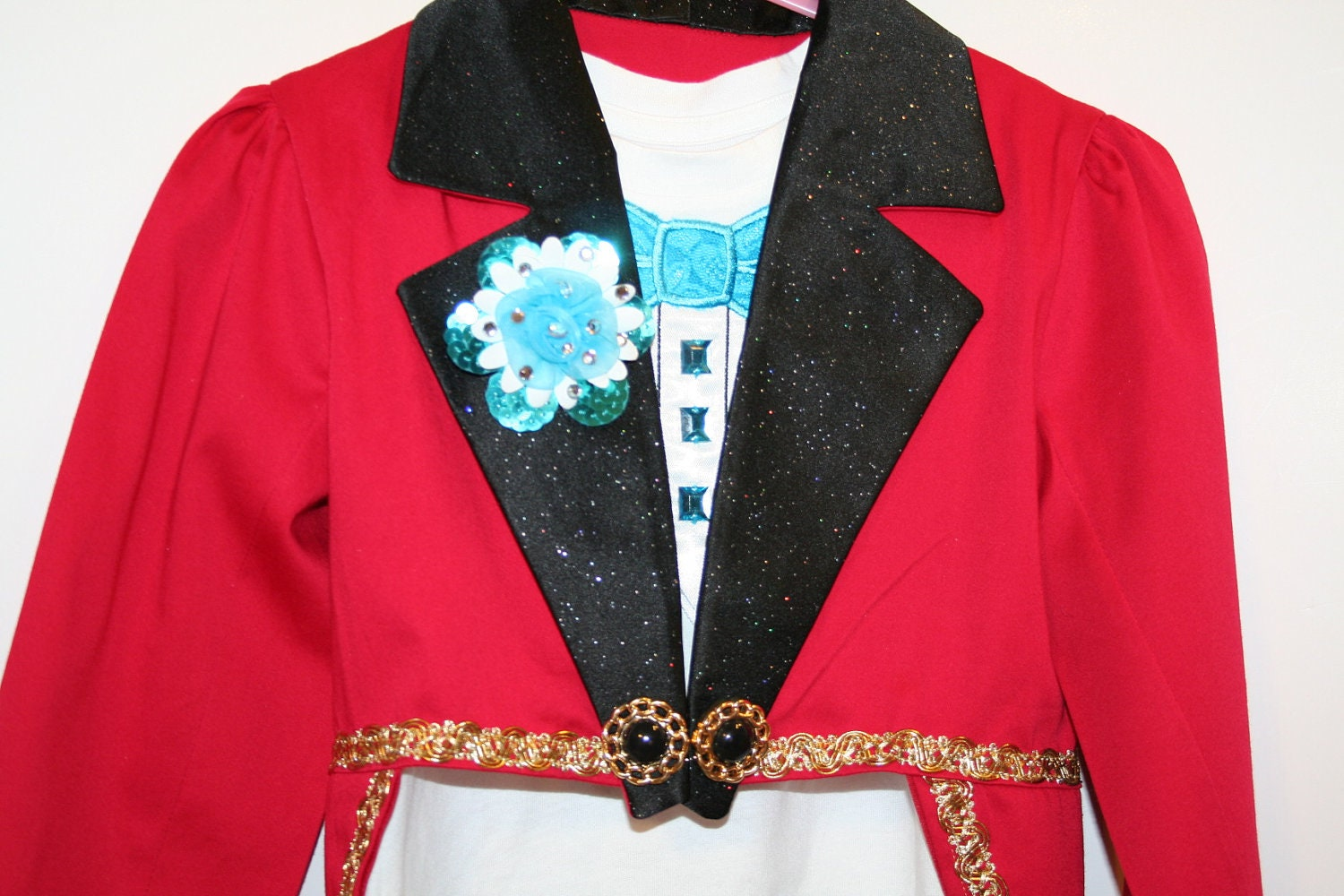 This two piece costume features a neoprene ringmaster tuxedo jacket with dazzling sequin spandex collar, cuffs and contrast lining with decorative gold buttons in front. Includes a cotton rib-knit tank top.