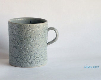Lace imprint teacup in ligh blue glaze.