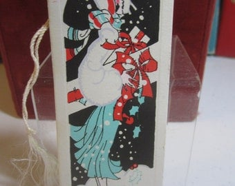 1920's unused art deco Gibson  bridge tally with christmas theme dark haired flapper  wearing cloche holding gifts in the snow holly berry