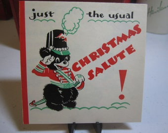 1930's art deco christmas card black bear dressed in a soldiers uniform and shooting a cannon ball holly berry hallmark