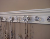 "Necklace holder.This stunning jewelry organizer w/ rhinestone center has 9 vintage inspired knobs on off white wood background 26 ""  long"
