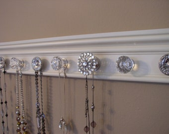 jewelry holder .This wall organizer has a rhinestone center knob total of  9 decorative knobs on off white wood background 26 inches long