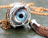 Blinking eyeball necklace wrapped in silver wire with a copper tassel on a copper chain