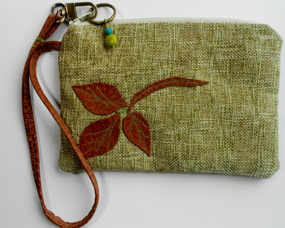 Green woven clutch or wristlet with leather trim.