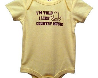 I'm Told I Like Country Music Graphic Baby Bodysuit