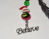 Christmas bookmark with feather crook, glass santa, and tibetan believe charm.