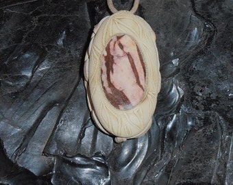 Earth Rhythm- This Spirit Amulet features a polished piece of African Jasper that is set in Cream colored leather with Carving.