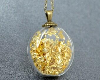 Gold leaf in flat round blown glass antique brass pendant