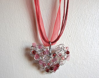 I Heart U. Valentine's Day crocheted wire heart pendant with pink cats eye and red beads on a red ribbon neck cord.