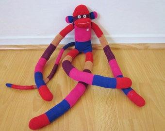 Knee sock monkey with rugby stripes in red, blue, purple, pink, and beige