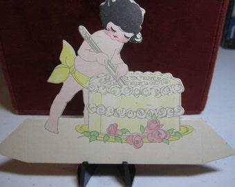 1920's art deco die cut Buzza wedding theme place card cherub girl with bobbed hair cutting a wedding cakee