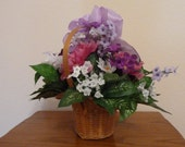 Floral Arrangement, A Beautiful Silk Floral  Arrangement in Pink, White and Lilac with a Lilac Fluffy Bow in a Tan Wicker Basket.
