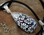Teardrop Shaped polymer  clay pendant silver top cap with a  18 inch suede cord black back ground white flower pattern