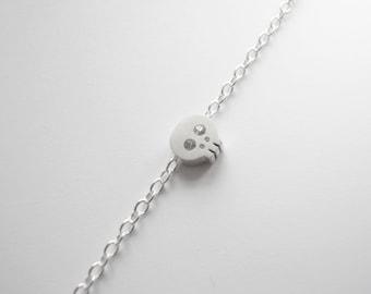 Silver bracelet with tiny skull bead pendant