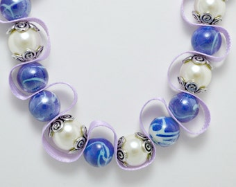Blue and white bead necklace with light purple ribbon. Beaded ribbon. Silver encased white pearls. Ships free to U.S.