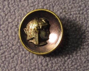 antique metal, pharoah face button, background is a purple toned metal