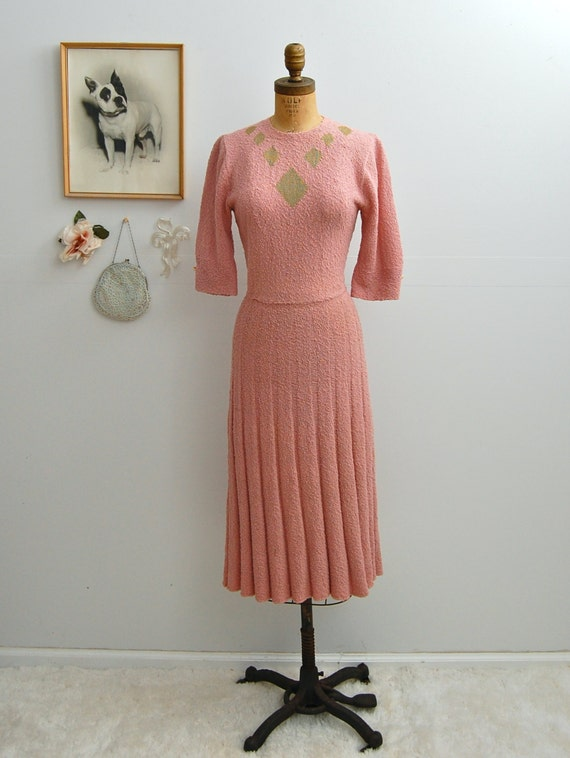 pink art deco knit dress with pleated skirt and diamond pattern neckline detail