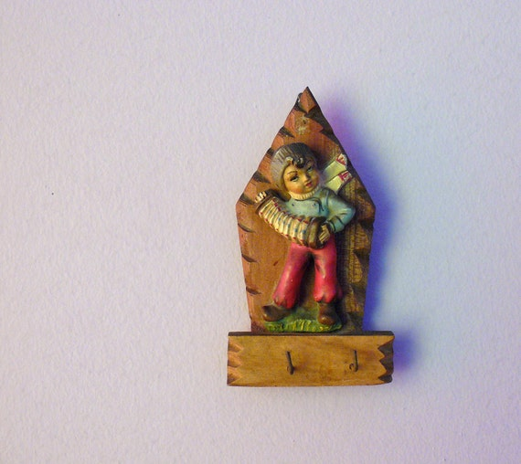 Vintage carved wood key hook. little boy playing piano accordion statuette. rustic key rack