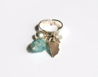 Modern silver statement ring with artistic movement of aquamarine stone, silver bead and sterling silver charms.- 'Blu Charm Ring'