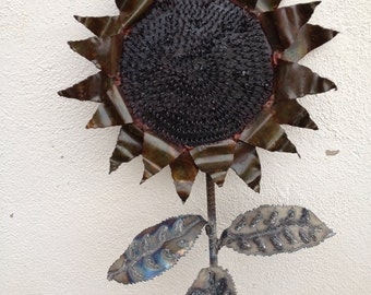 Metal sculpture of a sunflower with coiled center.