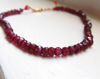 Garnet bracelet red silk thread gold delicate elegant January birthstone
