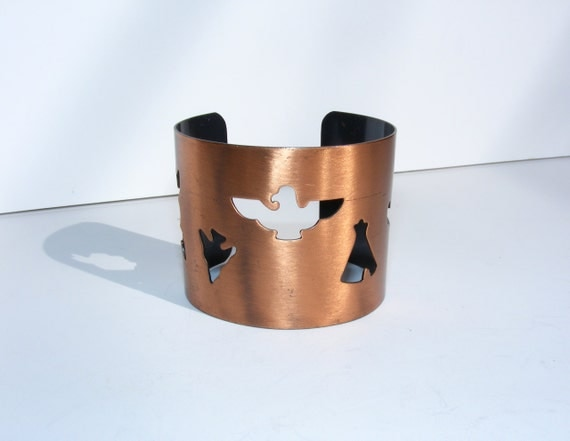 Vintage wide copper cuff with Native American motifs 1960s. Cut out arrowhead, eagle, teepee, canoe. Unworn vintage jewelry.