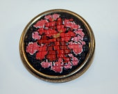 Small brooch in faux needlepoint technique of polymerclay flower design in base metal bezel.