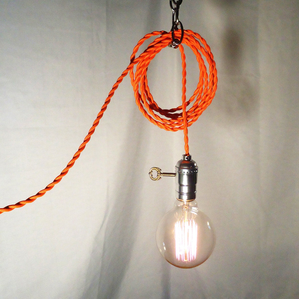 hanging lamp twisted orange cord exposed edison bulb