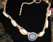 18 inch sun and cowrie shell hemp necklace with ceramic sun centerpiece.  Feel the summer beach