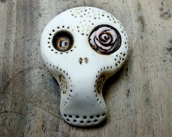 White sugar skull with a light pink rose in his eye. Brooch, keychain, pendant or magnet (you choose)