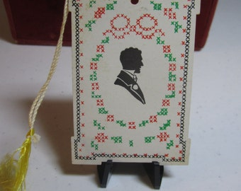 1930's -40's unused die cut bridge tally card silhouette of a victorian man on  a needlepoint designed background