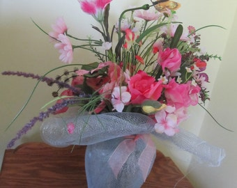 Pink Babys Breath, Onion Grass, Daisies, Roses, Lilies, Butterfly, and etc in a Vase Wrapped in Silver Decor Mesh with a Pink Bow