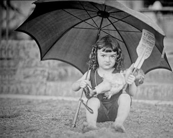1923 Vintage Image of Girl on Beach Holding Umbrella and Doll, 10x8