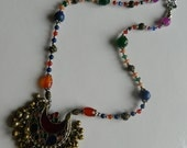 Richly coloured and textured necklace with tasseled pendant