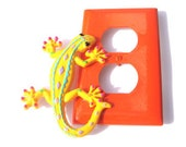 Yellow Tropical Gecko on a Bright Orange Outlet Plate