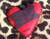 heart shaped small felt pillow hand stitched with a banner and the f%&k embroidered on