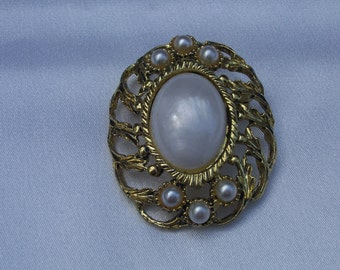 Gold toned pin with pearl caboshon enclosed in gold leaf swirled filigree and 6 faux pearls