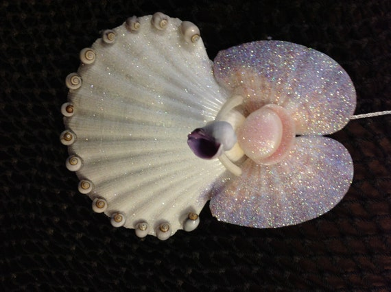 Angel holding a purple shell ornament with by seathingsventura for Seashell ornaments craft