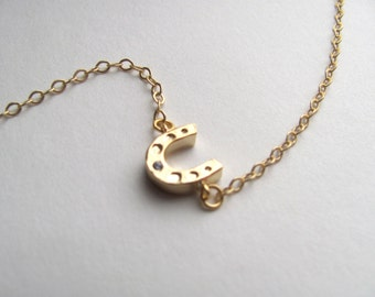Tiny gold lucky horse shoe charm necklace on delicate gold plated chain