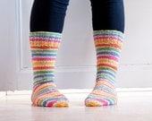 Hand knit socks in durable woolblend yarn in colorful stripes in pink, blue, green, yellow, orange. Floral meadow.