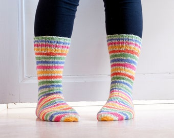 Hand knit socks in durable woolblend yarn in colorful stripes in pink, blue, green, yellow, orange. Floral meadow.