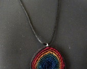 Handfelted rainbow mulberry silk and wool spiral pendant on a black satin cord necklace