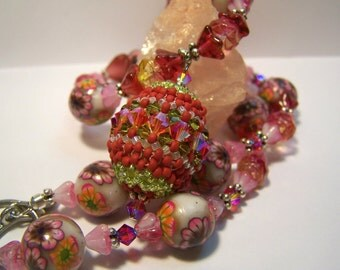 Beaded bead pendant on floral necklace featuring hand made beads in rust pink and green