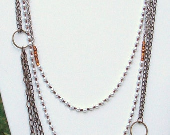 pearl and metallic continuous bead wrappable necklace paired with brass and bronze slip-on necklace
