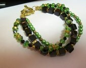 size 8  Fashionable, Fancy, Striking,  Green, Black and Gold 3 Strand Bracelet .... cubes, crystals and faux pearls ... Now only .99 US ship