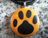Dog Print hand carved on a polymer clay Orange Pearl color background. Pendant comes with a FREE 3mm necklace