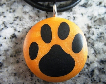 Dog Print hand carved on a polymer clay Orange Pearl color background. Pendant comes with a FREE necklace