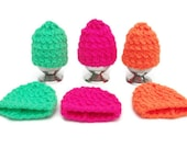 knitted egg cosies bright neon  pink, green and orange.