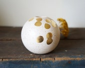speckled ball vessel with spotted gold leaf design